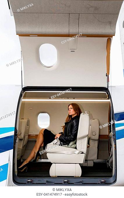 young beautiful woman in Luxury interior in bright colors of genuine leather in the business jet. The view through an open hatch