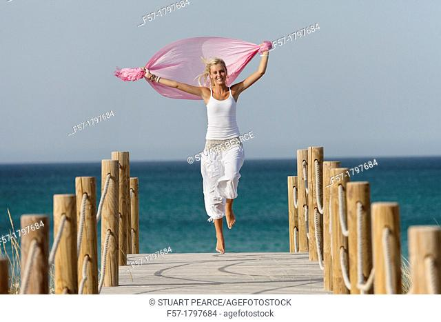 Healthy young woman skipping down a boardwalk