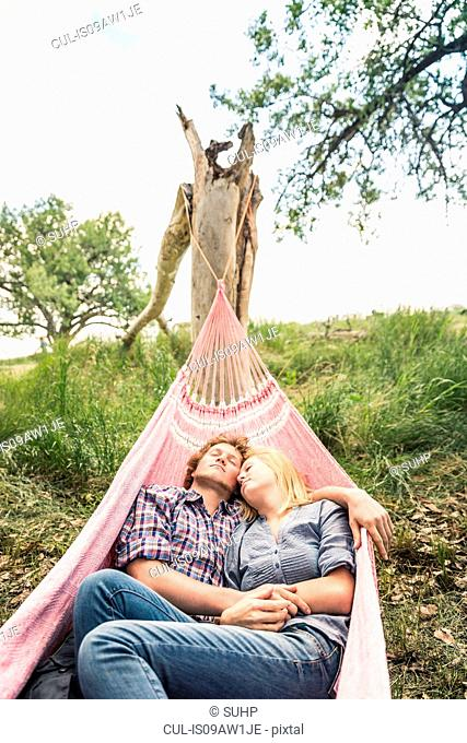 Romantic teenage girl and boyfriend reclining in rural hammock