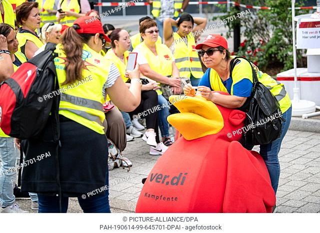 14 June 2019, Baden-Wuerttemberg, Neckarsulm: Striking Kaufland employees photograph themselves in front of the company's headquarters in Neckarsulm with the...