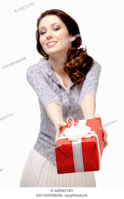 Young woman offers a gift wrapped in red paper, isolated on white