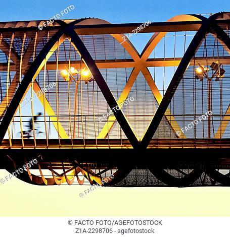Cyclist passing by the Arganzuela bridge, designed by architect Dominique Perrault. Madrid Rio Park. Madrid. Spain