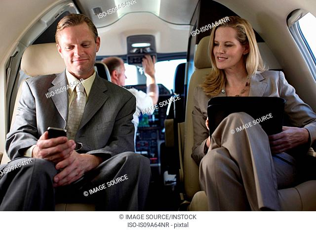 Business people talking in airplane