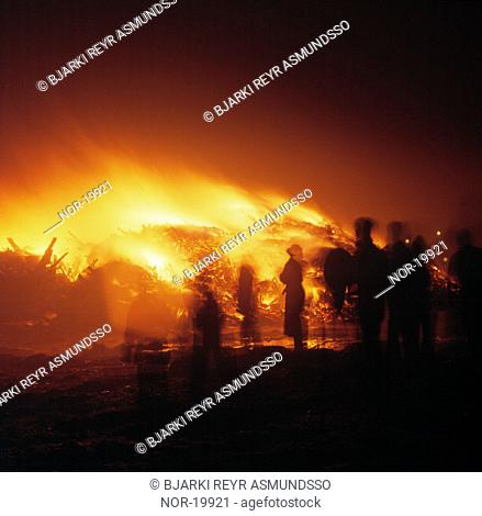 People standing close to a bonfire on New Year's Eve.  Iceland, southwest, Gardabaer