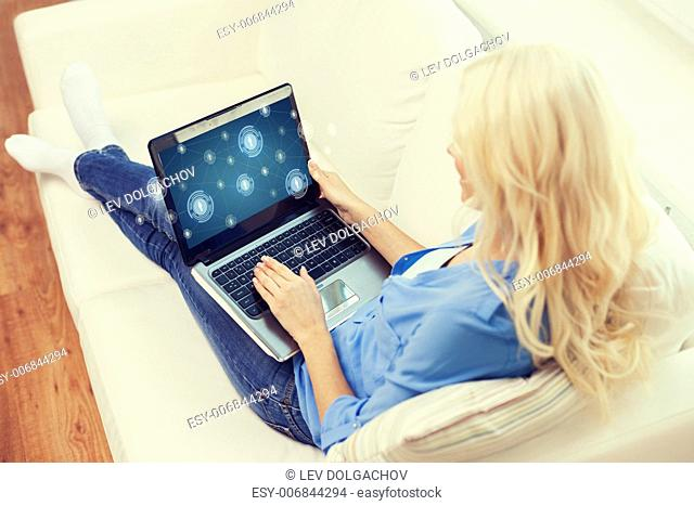 home, technology and internet concept - smiling woman with laptop computer sitting on couch at home
