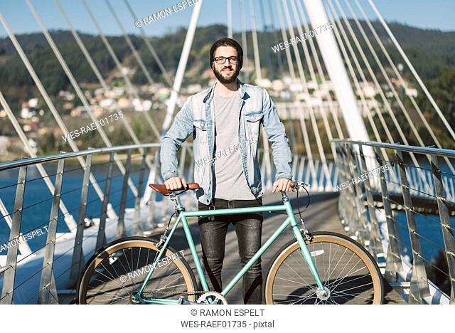 Smiling young man with his fixie bike on a bridge