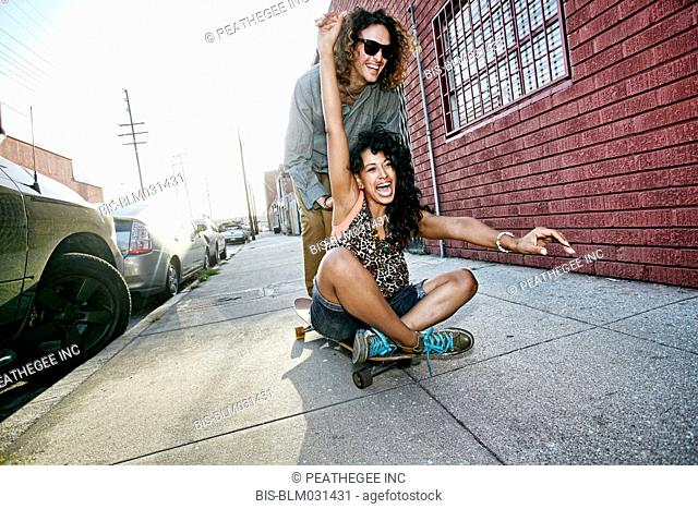 Couple riding skateboard on city street