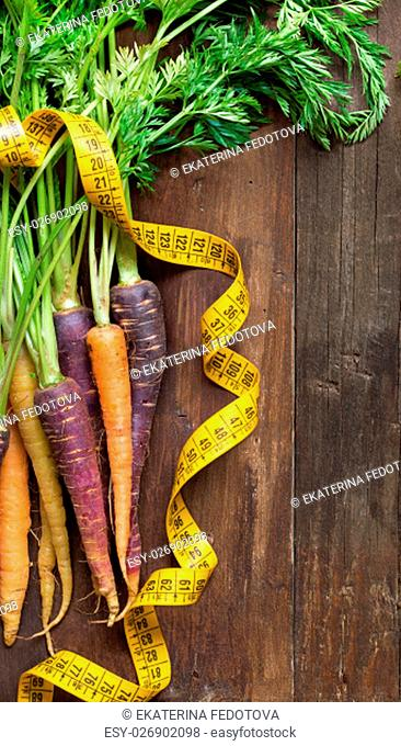 Fresh organic rainbow carrots and yellow measuring type on wood