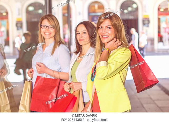 Happy Shopping Female Friends with bags on the street.Group of caucasian women purchasing in the city