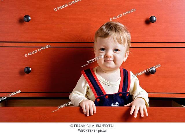 Baby boy playing inside cupboard drawer