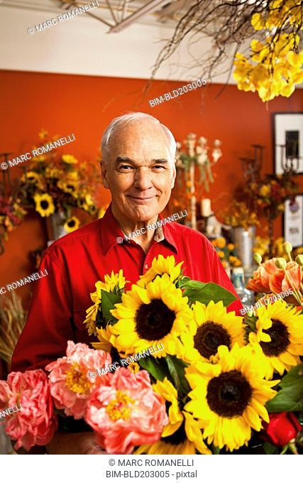 Caucasian florist with bouquet in shop