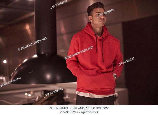 relaxed man with his hands in pockets of red sweater pullover, standing indoors in bar, alone, nightlife, Afghan ethnicity, in Munich, Germany
