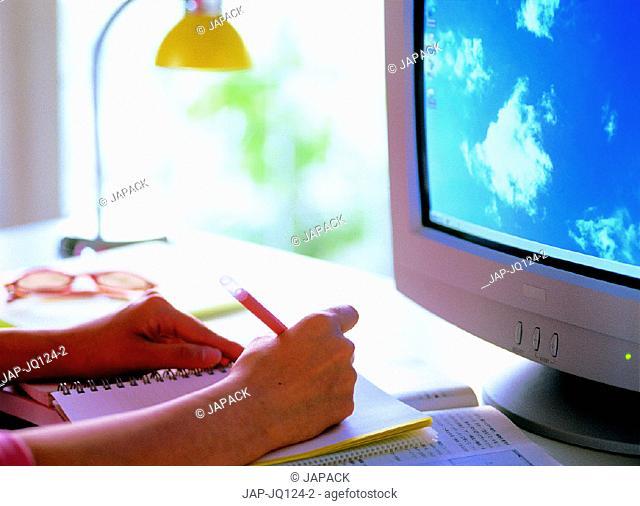 Hands and pen beside computer