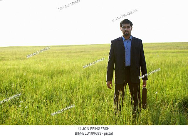Indian businessman with briefcase in field
