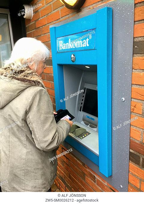 Elder woman getting money from a bancomat in Ystad, Sweden, Scandinavia