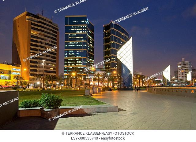 The seaside Larcomar Shopping Center and apartments illuminated at night in Miraflores, Lima, Peru, South America