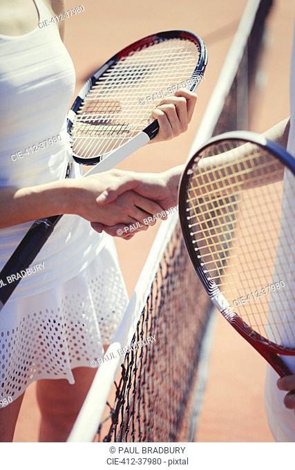 Tennis players handshaking in sportsmanship at net on sunny tennis court