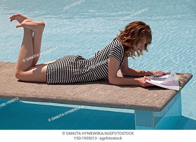 female student reading book, studying at the swimming pool, Geneva, Switzerland