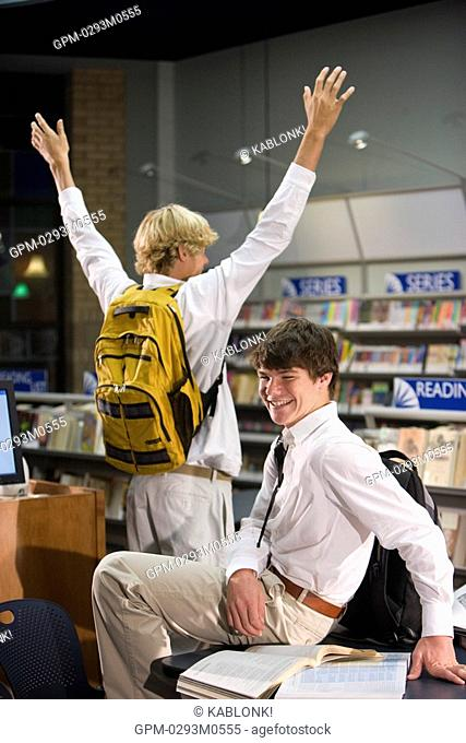 Two high school students messing about in library