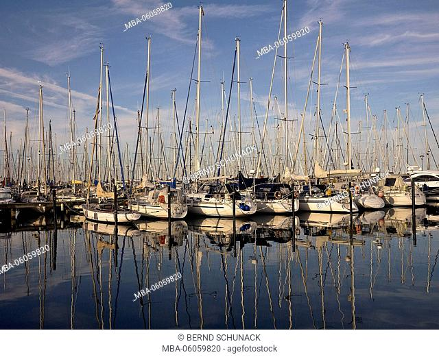 Ships in the yacht harbour of 'Heiligenhafen' are reflecting in the calm water at sundown