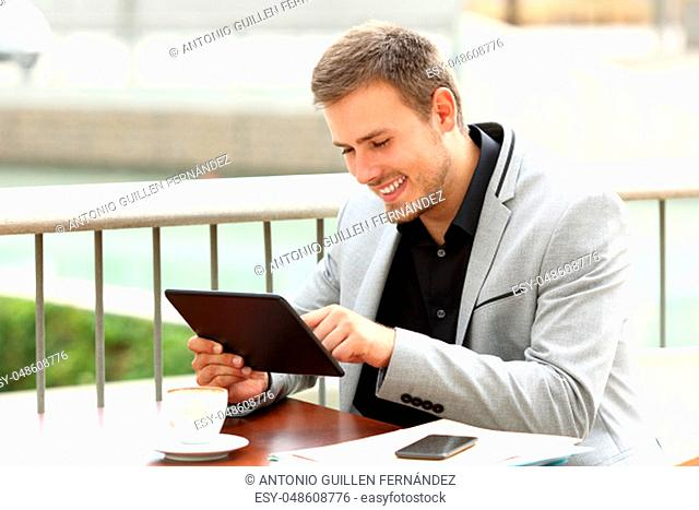 Single executive works on line with a tablet sitting in a coffee shop