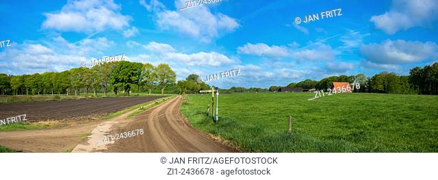 panorama of landscape with grassland, dirtroad, farm and plowed field at eastern holland