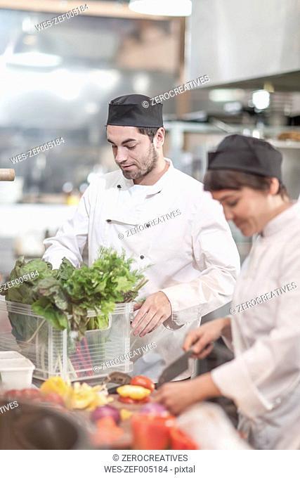 Two ches preparing food in restaurant kitchen
