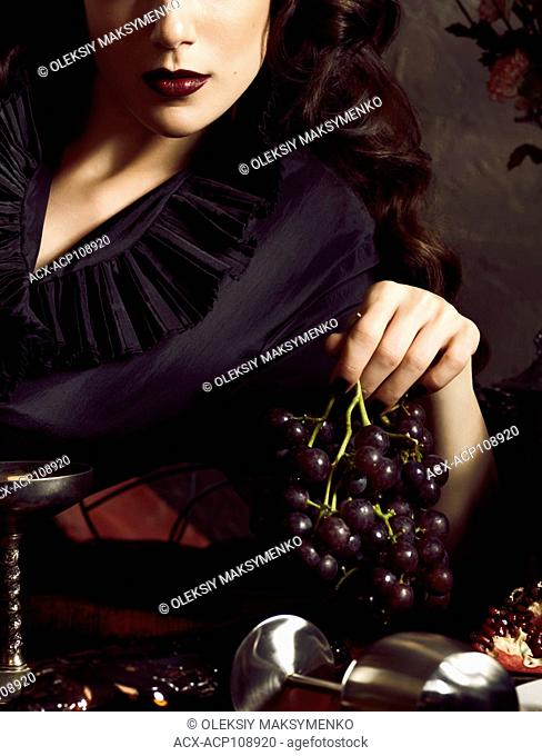 Artistic conceptual portrait of a beautiful woman holding grapes in her hand