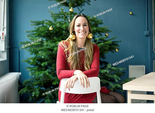 Portrait laughing woman wearing golden Christmas bauble earrings