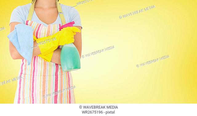Female cleaner standing with napkin and spray bottle against yellow background