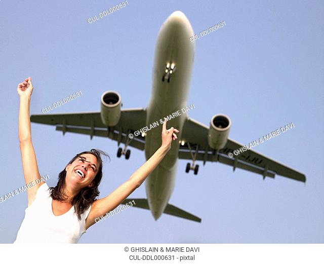 Woman smiling with arms outstretched standing below a plane flying overhead