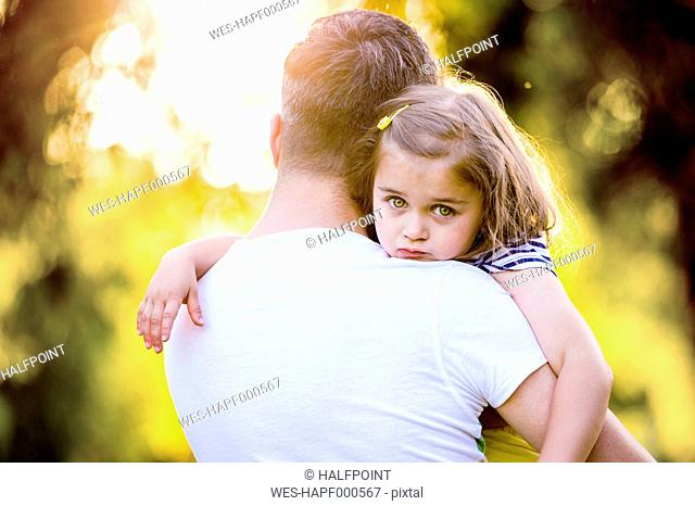 Portrait of sad little girl on father's arms