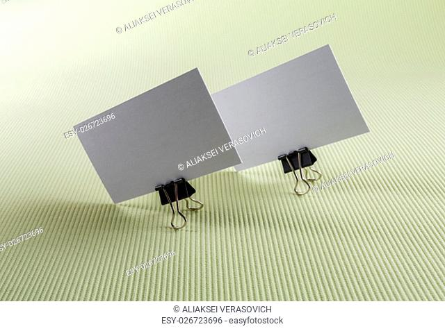 Two blank business card on green background