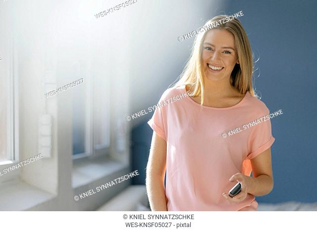 Portrait of smiling young woman with cell phone in her hand
