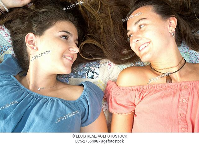 Two teenagers lying on a bed talking happily