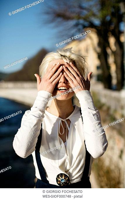 Italy, Verona, blond woman covering eyes with her hands