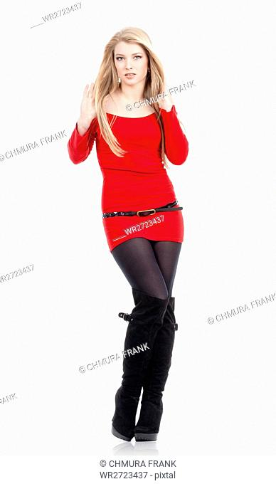 young woman with blond hair in red dress standing - isolated on white