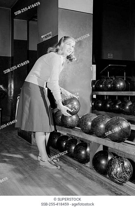 Smiling young woman holding bowling ball