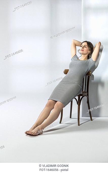 Young woman reclining on chair against white background
