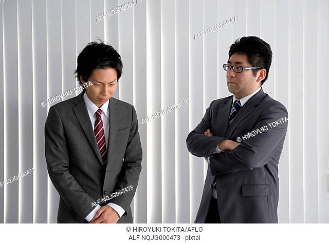 Young Japanese businessman being scored by his boss