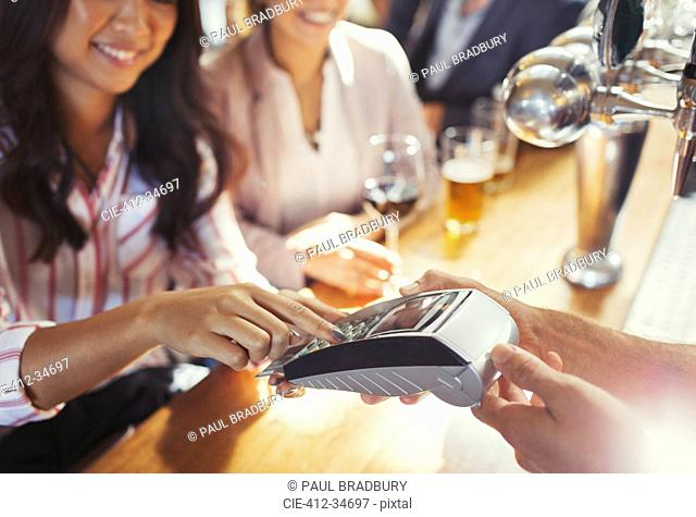 Woman paying bartender using credit card machine at bar