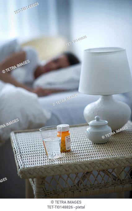 Sleeping pills bedside table with woman sleeping in background