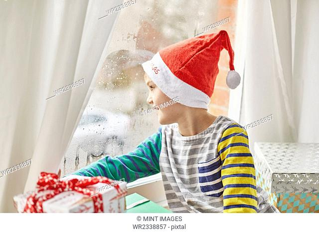 Christmas morning in a family home. A boy in a Santa hat looking out of a bedroom window