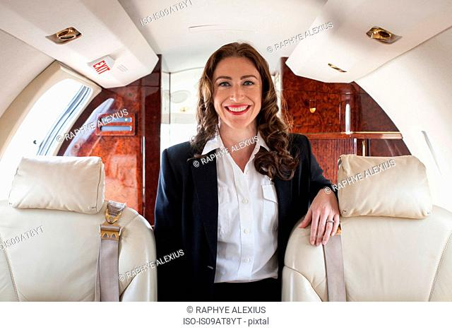 Portrait of female flight attendant on private jet