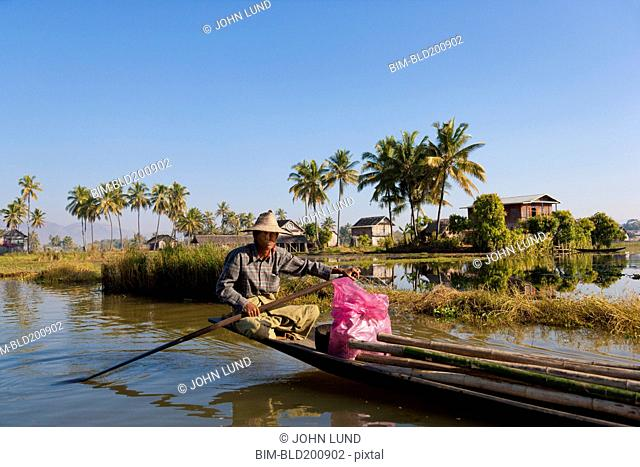 Burmese man rowing traditional boat