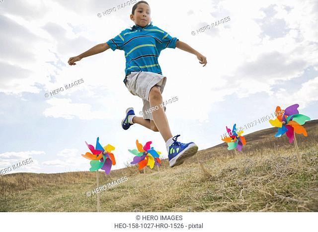 Schoolboy jumping over pinwheels on field