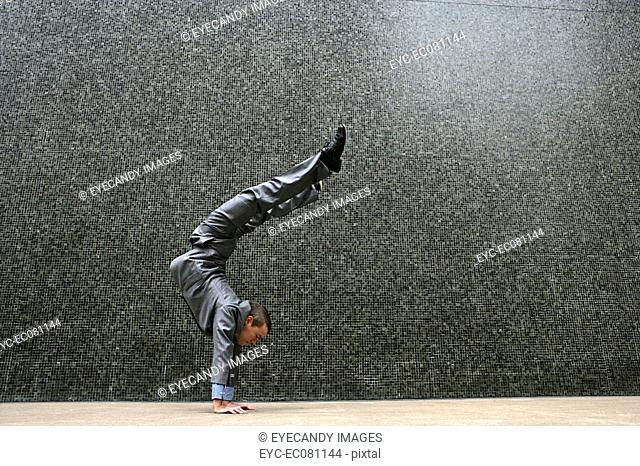 Young businessman doing handstand outdoors