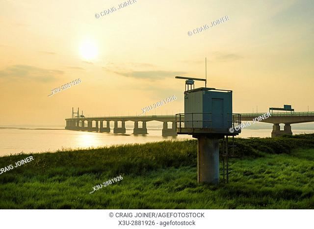 A shore-based radar tower at Severn Beach on the shore of the Severn Estuary with the Prince of Wales Bridge beyond, Gloucestershire, England