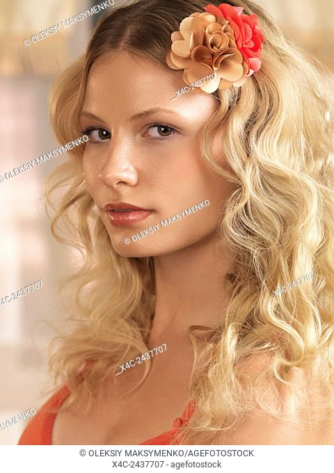 Beauty portrait of a young beautiful woman with a floral hairpiece in her golden blond hair