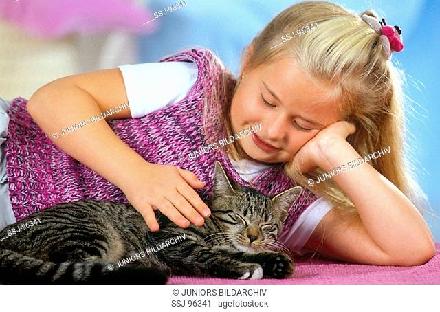 girl is patting a cat